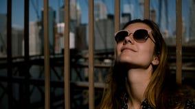 Close-upportret die van gelukkige Kaukasische vrouw die in zonnebril in de hemel, van zonnige dag genieten de Brug van Brooklyn 4 stock video
