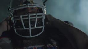 Close-upportret die van het gebaarde Amerikaanse voetbalster zetten op helm op het hoofd, in camera met rust kijken stock videobeelden