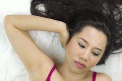 Close-upportret die van humeurige Aziatische vrouwen op grond met zwart lang haar liggen verstoord acteren, ongelukkig royalty-vrije stock afbeeldingen