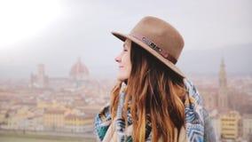 Close-upportret die van jong mooi Kaukasisch meisje in hoed gelukkig glimlachen, camera in Florence op een mistige dag bekijken stock videobeelden
