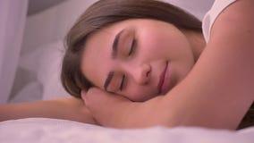 Close-upportret die van jong overweldigend Kaukasisch wijfje op het bed liggen die camera en het dagdromen bekijken stock video