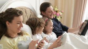 Close-upportret die van Jonge Familie op het Bed in de Ochtend liggen en Hun Gadgets gebruiken Ouders en Jonge geitjes het Dragen stock video