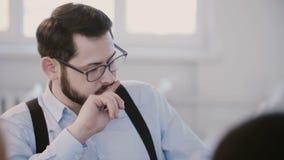 Close-upportret die van jonge succesvolle ernstige zakenman die koffie hebben, op de moderne vergadering van het werkplaatsbureau stock footage