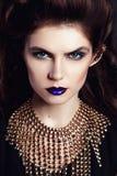 Close-upportret met diep blauw oog, creatieve make-up en gouden toebehoren Stock Foto's