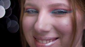 Close-upportret in profiel die van blond model aan camera draaien en in camera op vage lichtenachtergrond glimlachen stock footage
