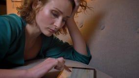 Close-upportret in profiel van het vermoeide gember krullend-haired meisje liggen op bank en het typen op tablet zorgvuldig op co stock videobeelden