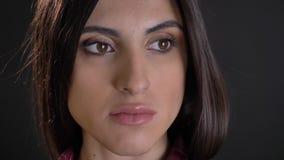 Close-upportret in profiel van Kaukasisch langharig donkerbruin meisje die calmly op in afstand op zwarte achtergrond letten stock footage