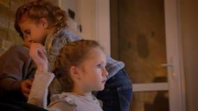 Close-upportret in profiel van kleine Kaukasische meisje het letten op film aandachtig en haar zuster die de bank in comfortabel  stock video