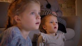 Close-upportret in profiel van kleine Kaukasische meisjes die op film met groot vermaak in comfortabele huisatmosfeer letten stock video