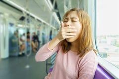 Close-upportret slaperig, geeuw, dichte ogen jonge vrouw in hemeltra stock foto's