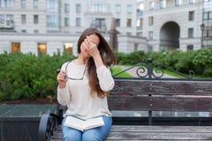 Close-upportret van aantrekkelijk wijfje met in hand oogglazen Het slechte jonge meisje heeft kwesties met visie Zij wrijft haar  royalty-vrije stock foto