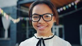 Close-upportret van aantrekkelijke Afrikaanse Amerikaanse tiener in glazen het glimlachen stock videobeelden