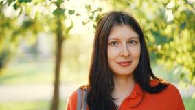 Close-upportret van aantrekkelijke jonge vrouw die camera en het glimlachen status in park op zonnige de zomerdag bekijken Groen stock videobeelden