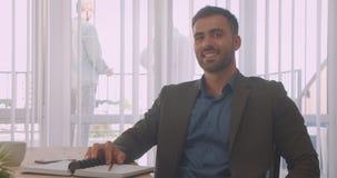 Close-upportret van aantrekkelijke zakenman die camera bekijken die gelukkig in het bureau binnen op de werkplaats glimlachen stock video