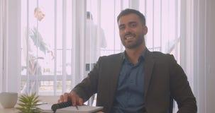Close-upportret van aantrekkelijke zekere zakenman die camera in het bureau binnen op de werkplaats bekijken stock video