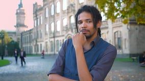 Close-upportret van Afrikaans-Amerikaanse student met dreadlocks zorgvuldig wat betreft zijn baard op universitaire achtergrond stock video