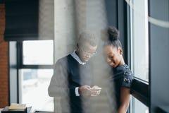 Close-upportret van Afrikaans paar die gardget op het werk gebruiken royalty-vrije stock foto