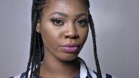 Close-upportret van Afrikaanse vrouw in ontzetting in grijze studio stock videobeelden