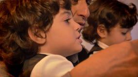 Close-upportret van Arabische vader op middelbare leeftijd in profiel het spelen met zijn tweelingzonen trifling met speelgoed in stock footage