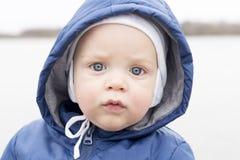 Close-upportret van babyjongen die camera bekijken Leuke zuigelingsjongen in een hoed en een kap Mistig dalingseiland royalty-vrije stock fotografie