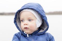 Close-upportret van babyjongen die camera bekijken Leuke zuigelingsjongen in een hoed en een kap Mistig dalingseiland stock fotografie