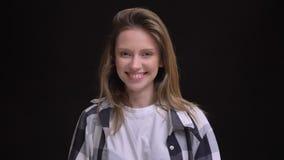 Close-upportret van blij jong Kaukasisch langharig meisje in plaidoverhemd die oprecht in camera op zwarte glimlachen stock videobeelden