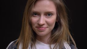 Close-upportret van blij jong Kaukasisch langharig meisje in plaidoverhemd die schuchter in camera op zwarte glimlachen stock video