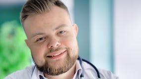 Close-upportret van blonde mens arts met baard en het modieuze kapsel vriendschappelijke glimlachen stock video
