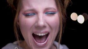 Close-upportret van blondemeisje met kleurrijke samenstelling die groot geluk emotioneel op vage lichtenachtergrond tonen stock video