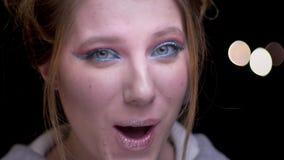 Close-upportret van blondemeisje met kleurrijke samenstelling die positief vermaak childishly op vage lichten tonen stock footage