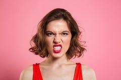 Close-upportret van boze jonge vrouw die met rode lippen bekijken Stock Foto
