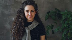 Close-upportret van camera onderzoeken en yougn aantrekkelijk meisje die terwijl status tegen grijze muur en groot glimlachen stock footage