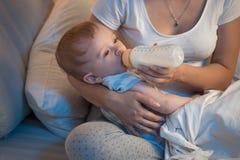 Close-upportret van 9 van de babymaanden oud jongen die melk van fles eten bij nacht Royalty-vrije Stock Afbeeldingen
