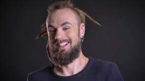 Close-upportret van de freaky Kaukasische mens met dreadlocks die positief vermaak en geluk op zwarte achtergrond tonen stock videobeelden