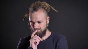 Close-upportret van de freaky Kaukasische mens met dreadlocks en het doordringen zorgvuldig wat betreft zijn baard op zwarte stock video