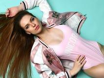 Close-upportret van de gelukkige liggende hoogste mening van de manier donkerbruine vrouw in het roze vest van het glamourlichaam Royalty-vrije Stock Afbeelding
