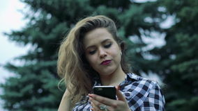 Close-upportret van de handen die van de meisjesbehandeling telefoon met behulp van door groene boomachtergrond langzaam stock videobeelden