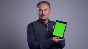 Close-upportret van de hogere Kaukasische mens gebruikend de tablet en tonend het groene scherm aan de camera stock footage