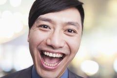 Close-upportret van de jonge mens die, Peking lachen stock foto