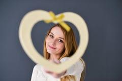 Close-upportret van de jonge vrouwelijke die vorm van het holdingshart op grijze achtergrond wordt geïsoleerd stock afbeelding