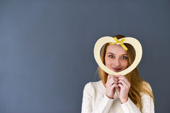 Close-upportret van de jonge vrouwelijke die vorm van het holdingshart op grijze achtergrond wordt geïsoleerd stock foto