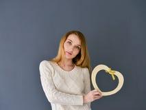 Close-upportret van de jonge vrouwelijke die vorm van het holdingshart op grijze achtergrond wordt geïsoleerd royalty-vrije stock afbeeldingen