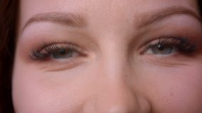 Close-upportret van de Kaukasische wavy-haired rollende ogen die van de blondeleraar vast op in camera bij bibliotheek letten stock video