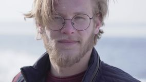 Close-upportret van de knappe gebaarde mens die in glazen met blond haar in de camera kijken die in openlucht glimlachen leisure stock videobeelden