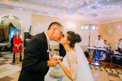 Close-upportret van de kussende jonggehuwden die de plaat met de plak van de wedcake houden royalty-vrije stock foto's