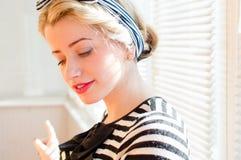 Close-upportret van de mooie blonde dame die van het pinupmeisje pret heeft die weg het gelukkige glimlachen richt die neer op he Royalty-vrije Stock Afbeelding