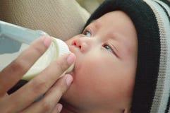 Close-upportret van de mooie consumptiemelk van de babyjongen van zijn moeder van het voeden van fles royalty-vrije stock afbeelding