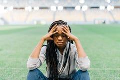 Close-upportret van de nadenkende Afro-Amerikaanse sportgirlzitting op het gras en het leunen op de knieën stock afbeelding