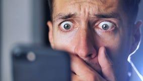 Close-upportret van de verraste mens die onverwacht nieuws op zijn smartphone lezen stock videobeelden