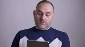 Close-upportret van de volwassen Kaukasische mens die de tablet gebruiken die dan camera en het glimlachen bekijken stock video